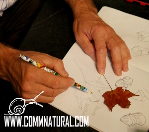 Workshop participant sketches leaves and acorns using tracing and blind contour techniques.
